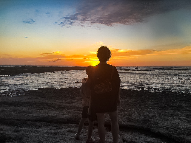 mother and daughter holding each other, standing on a sandy beach watching the sunset