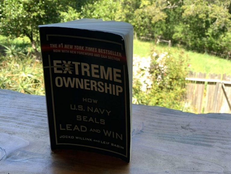 Extreme OwnershipHow US Navy Seals Lead and Win By Jocko Willink and Leif Babin book standing vertically on a wooden table with green yard in background