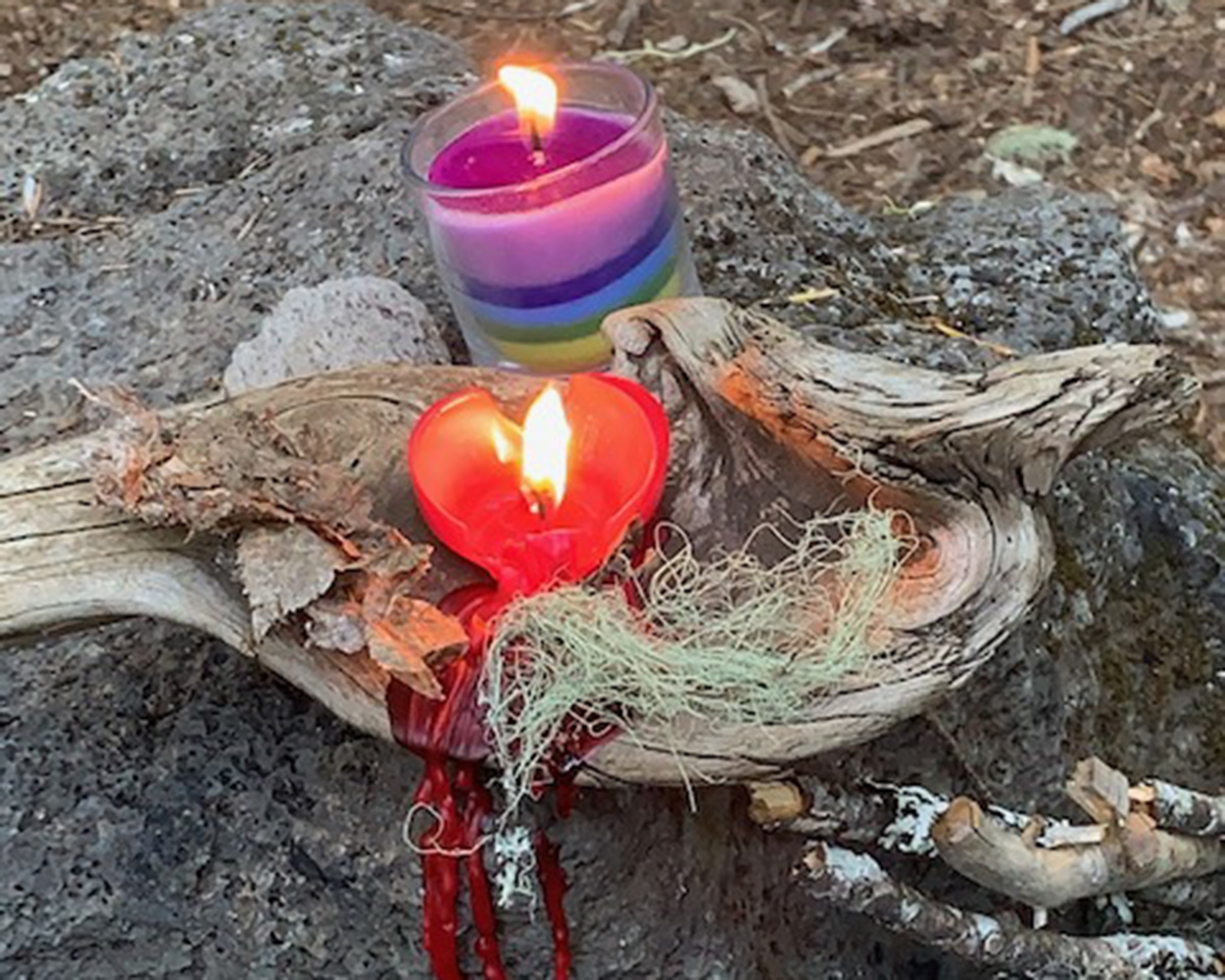 Rainbow and red heart-shaped candle burning with red wax dripping down wooden alter